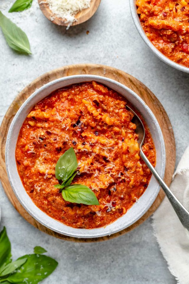 lasagna soup served in a bowl and garnished with parmesan cheese and fresh basil