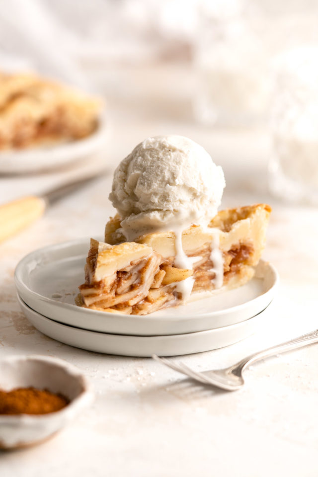 slice of pear pie on a small white plate topped with vanilla ice cream