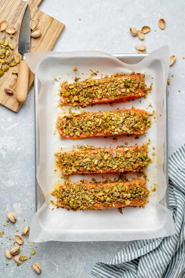 uncooked salmon topped with chopped pistachios on a baking sheet pan