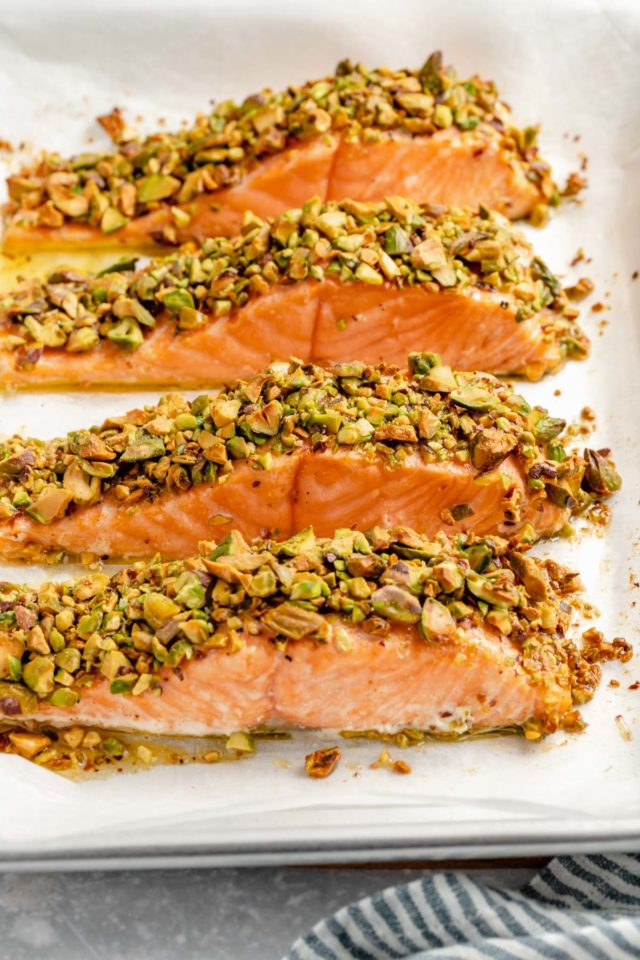 pistachio-crusted salmon on a parchment-lined baking sheet