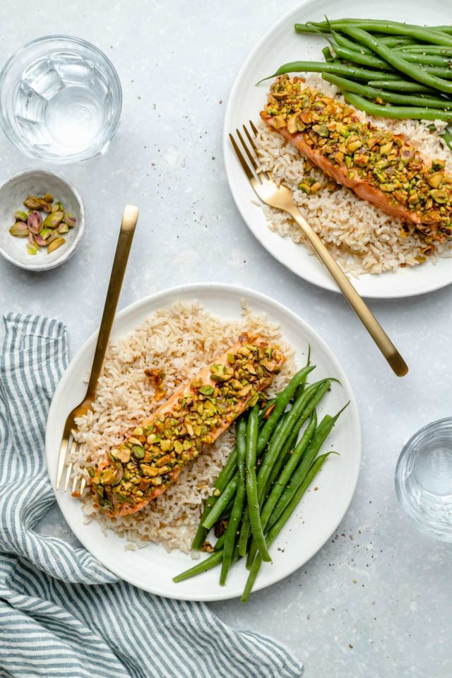 two plates with rice, green beans and pistachio-crusted salmon