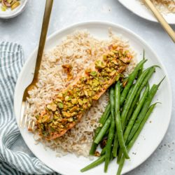 Pistachio-Crusted Salmon served on a plate with rice and green beans