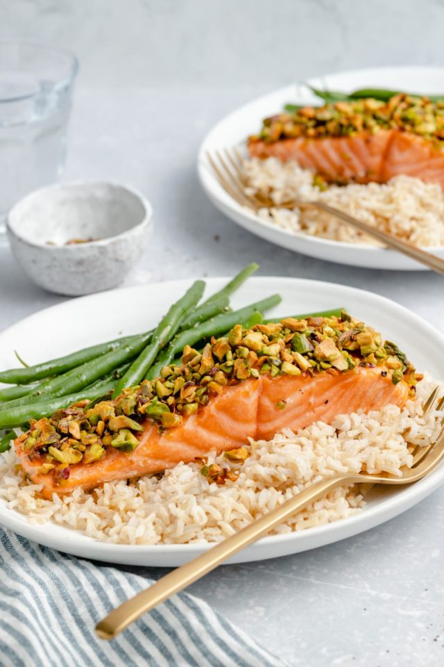 pistachio-crusted salmon on a plate with rice and green beans