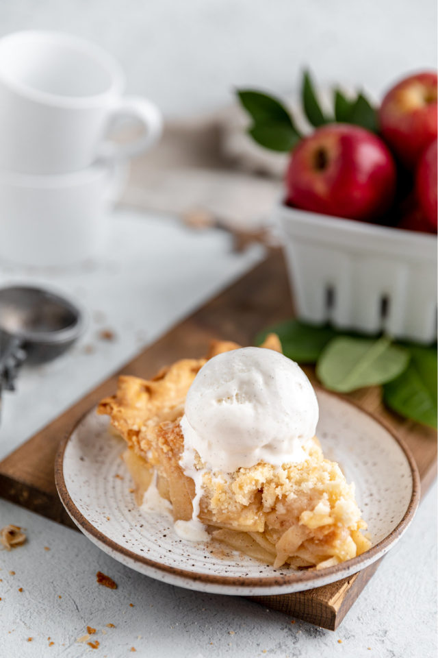 slice of apple crumb pie topped with a scoop of melting vanilla ice cream