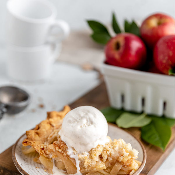 slice of apple crumb pie topped with a scoop of vanilla ice cream
