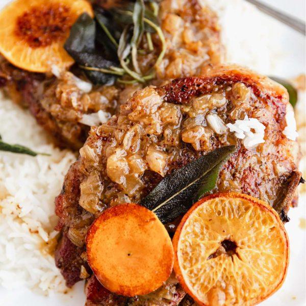 crock pot pork chops served with rice and garnished with orange slices