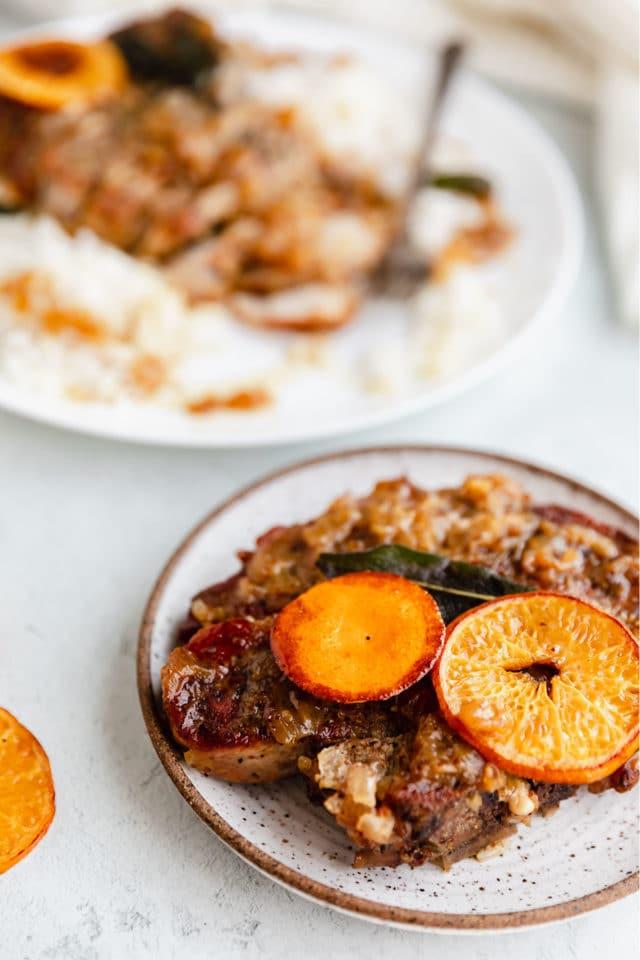 pork chops on a plate with an orange garnish