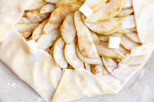adding pear slices over pie crust dough