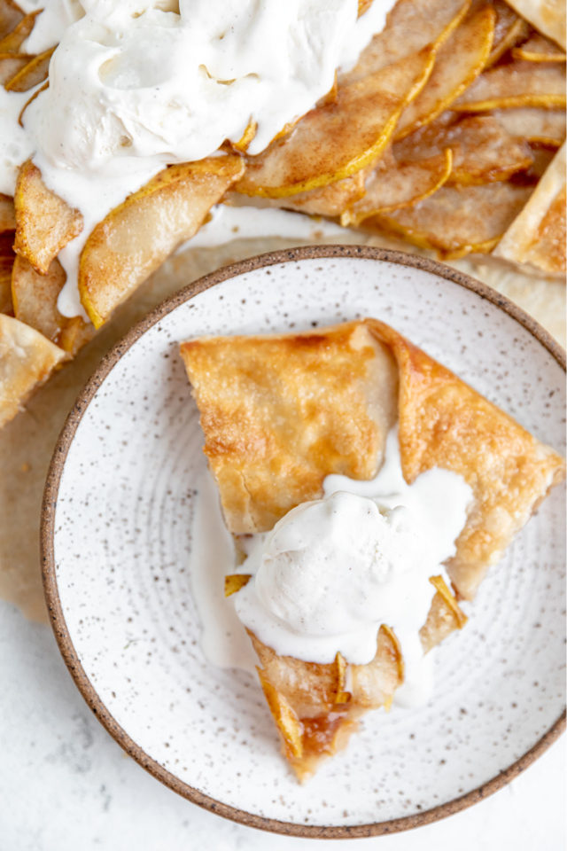 slice of pear galette on a plate with vanilla ice cream