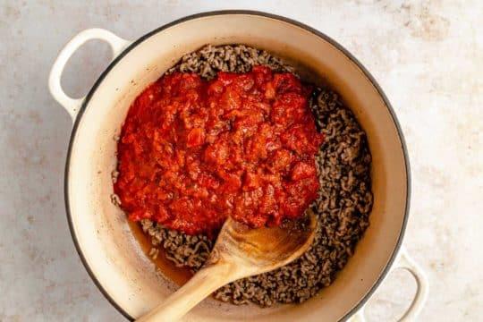 stirring marinara sauce into ground beef