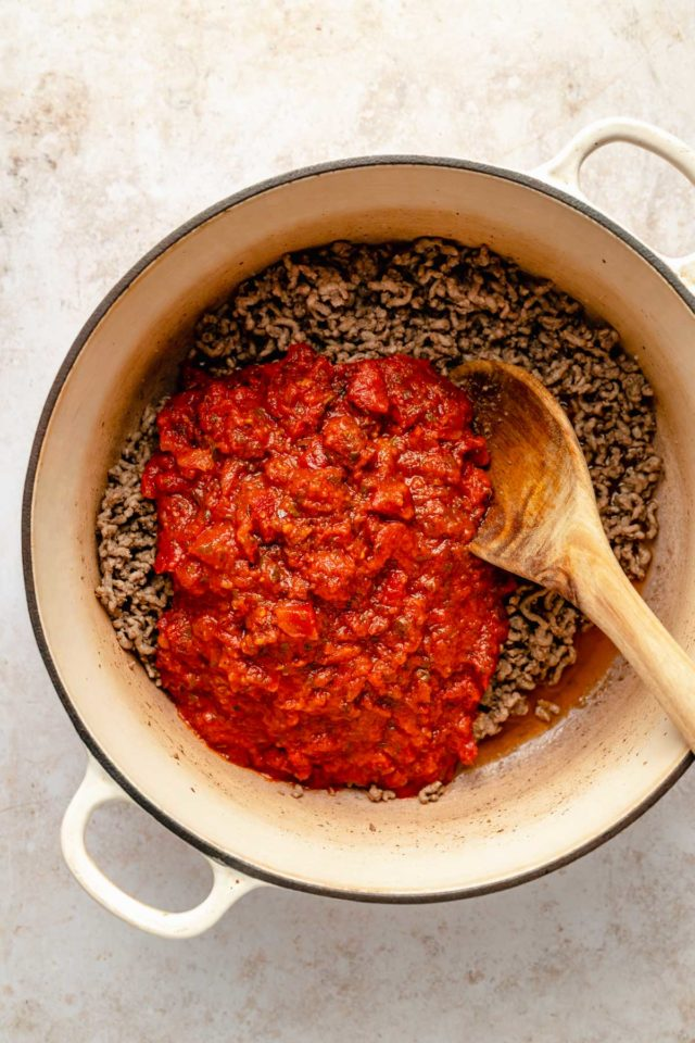 stirring marinara sauce in with ground beef