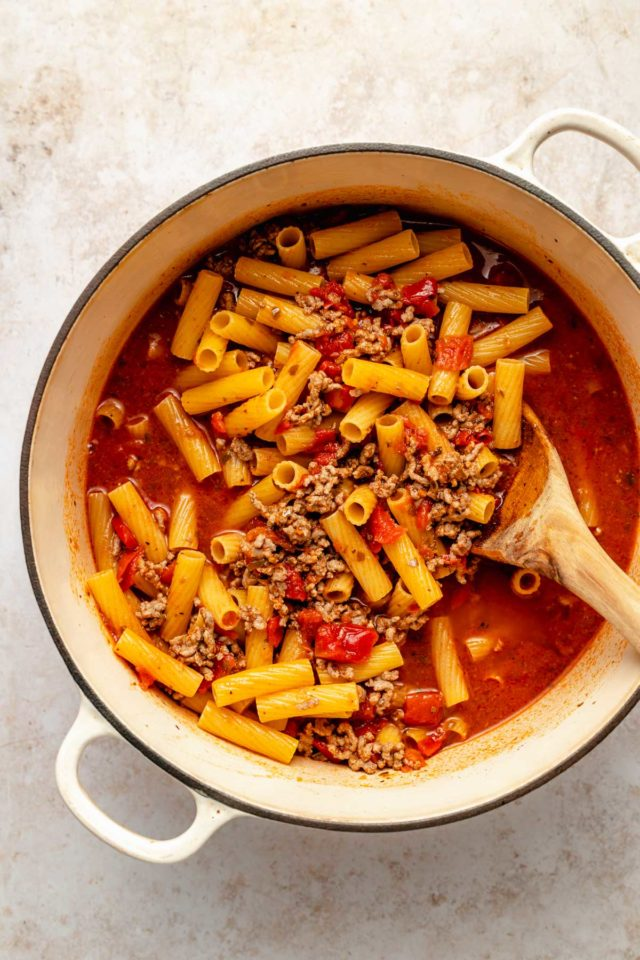 making one pot pasta in a Dutch oven with pasta and meat sauce