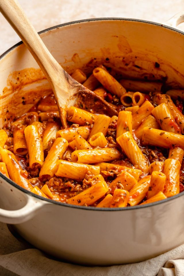 using a wooden spoon to stir one pot pasta recipe in a large pot