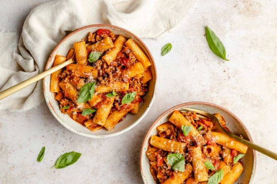 serving one pot pasta in two bowls garnished with fresh basil