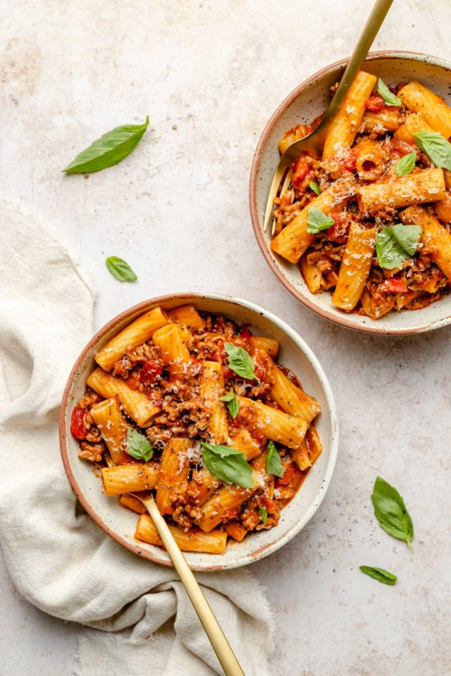 two bowls filled with pasta and meat sauce