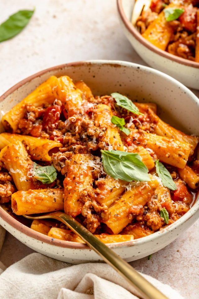 pasta with meat sauce garnished with fresh basil
