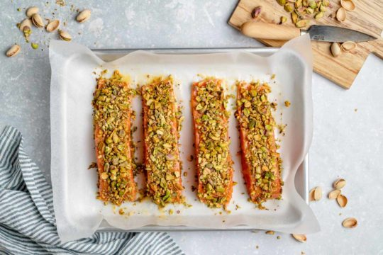 salmon topped with pistachios on a baking sheet pan