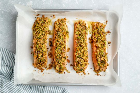 baked salmon topped with pistachios on a sheet pan