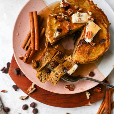 pumpkin pancakes topped with butter, syrup and chopped pecans